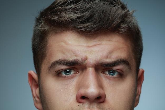 灰色のスタジオの背景に分離された若い男のクローズアップの肖像画。白人男性モデルの顔と青い目。男性の健康と美容、セルフケア、ボディケア、スキンケアのコンセプト。怒って、しわがあります。