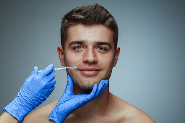 灰色のスタジオの背景に分離された若い男のクローズアップの肖像画。充填手術手順。男性の健康と美容、美容、セルフケア、ボディケア、スキンケアのコンセプト。老化防止。