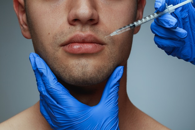 灰色のスタジオの背景に分離された若い男のクローズ アップの肖像画。充填手術手順。男性の健康と美容、美容、セルフケア、ボディケア、スキンケアのコンセプト。老化防止。