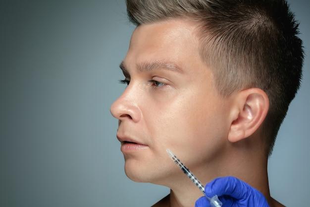 Крупным планом портрет молодого человека, изолированного на серой стене студии в процедуре заполнения хирургии