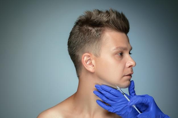 회색 벽에 고립 된 젊은 남자의 클로즈업 초상화. 충전 수술 절차, 입술 및 광대뼈. 남성의 건강과 미용, 미용, 신체 및 피부 관리의 개념. 노화 방지.