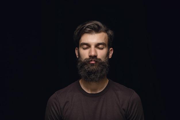 黒のスタジオで若い男の肖像画をクローズアップ