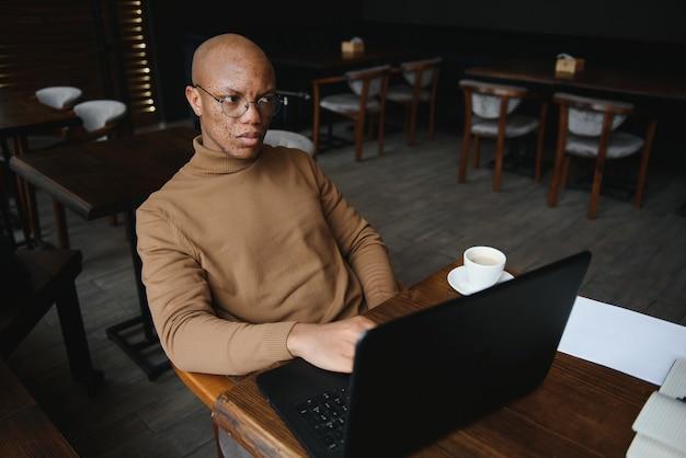 Крупным планом портрет молодого человека, сидящего в кафе, работающего на портативном компьютере