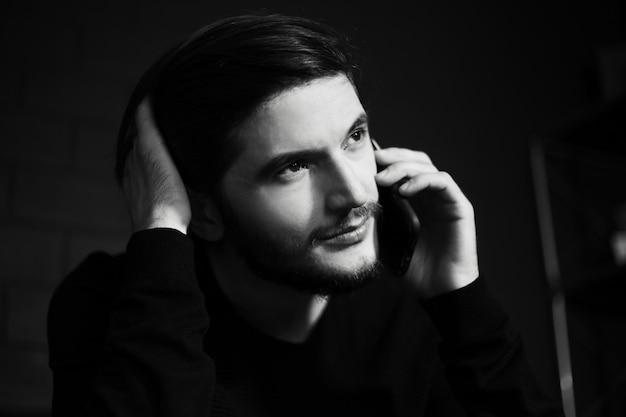 スマートフォンで話している若い男のクローズアップの肖像画。黒と白の写真。