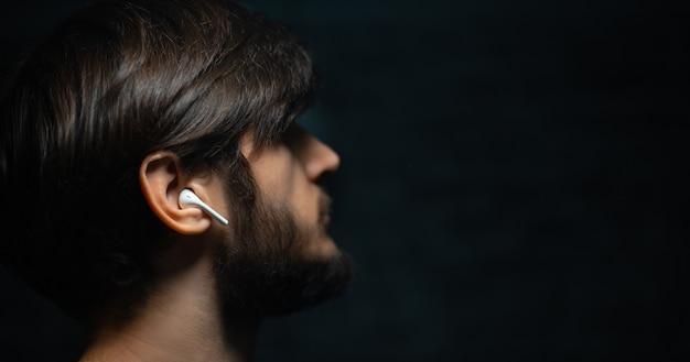 무선 이어폰을 사용하는 젊은 남자의 클로즈업 초상화