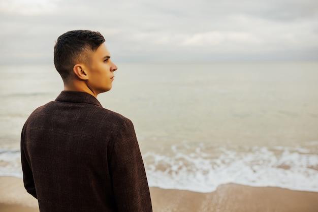 水に向かってビーチを歩いている若い男のクローズアップの肖像画。