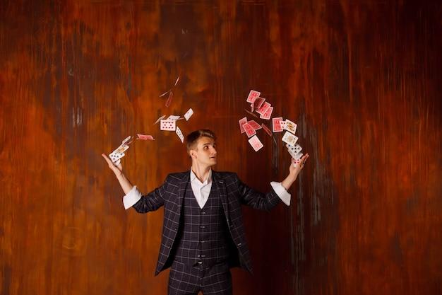 Крупным планом портрет молодого человека с азартными играми. красивый парень показывает фокусы с картой. умные руки фокусника на коричневой предпосылке текстуры. понятие о развлечениях и увлечениях. авторские права