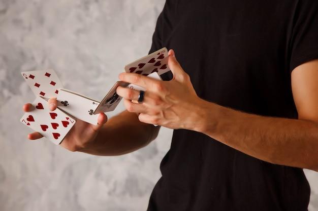 Крупным планом портрет молодого человека с азартными играми. красивый парень показывает фокусы с картой. умные руки фокусника на серой предпосылке текстуры. понятие о развлечениях и увлечениях. авторские права