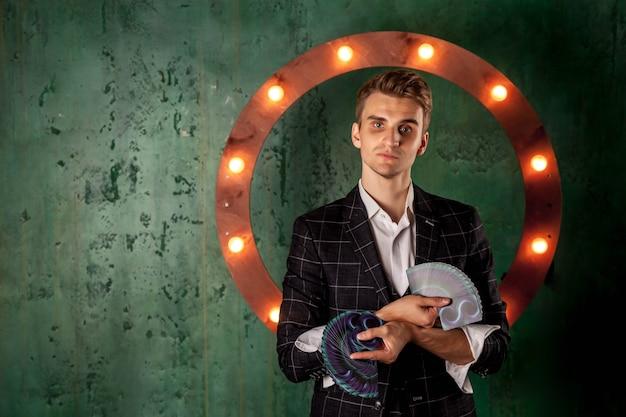 Крупным планом портрет молодого человека с азартными играми. красивый парень показывает фокусы с картой. умные руки фокусника на зеленой предпосылке текстуры. понятие о развлечениях и увлечениях. копировать пространство
