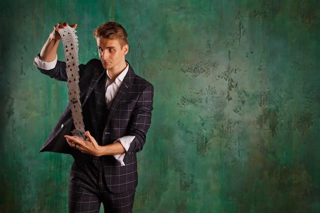 Крупным планом портрет молодого человека с азартными играми. красивый парень показывает фокусы с картой. умные руки фокусника на зеленой предпосылке текстуры. понятие о развлечениях и увлечениях. авторские права