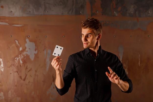 Крупным планом портрет молодого человека с азартными играми. красивый парень показывает фокусы с картой. умные руки фокусника на металлической предпосылке текстуры. понятие о развлечениях и увлечениях. авторские права