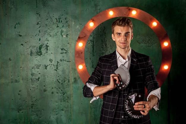Крупным планом портрет молодого человека с азартными играми. красивый парень показывает фокусы с картой. умные руки фокусника