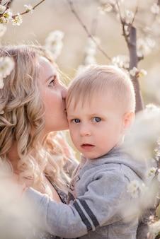 Крупным планом портрет молодой матери с маленьким белокурым сыном, которые обнимаются