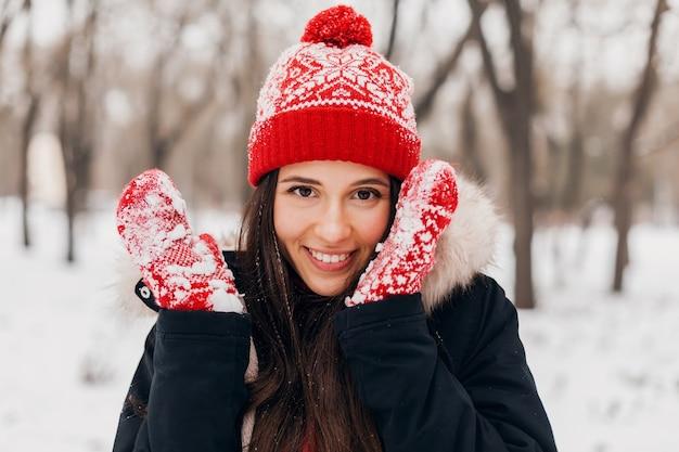 赤いミトンとニット帽を身に着けている若いかなり率直な笑顔の幸せな女性の肖像画をクローズアップ雪の中で公園で遊んで、暖かい服を着て、楽しんで歩いて毛皮のコートを着て