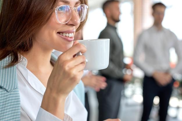 オフィスでコーヒーを飲む若いかなり白人のビジネス女性のクローズアップの肖像画
