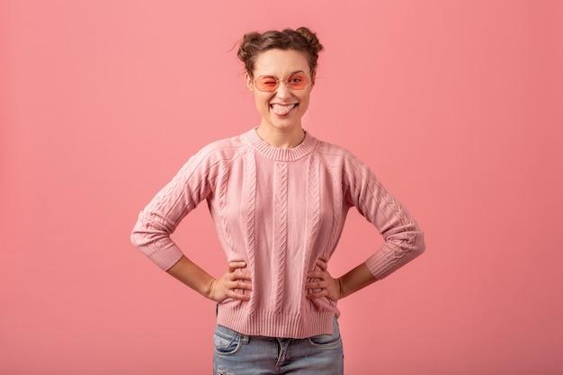 Крупным планом портрет молодой довольно милой улыбающейся женщины с забавным выражением лица, показывающей язык в розовом свитере и солнцезащитных очках, изолированных на розовом фоне студии, дурачиться