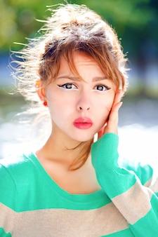 若い可愛い女の子のクローズアップの肖像画は、強力な感情を持って、驚いてショックを受けて、楽しんで、明るいセーターを着て、メイクアップします。