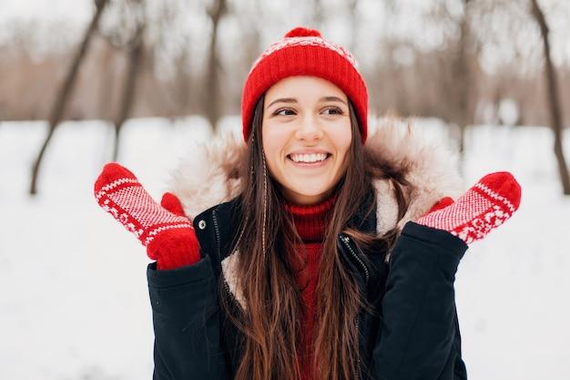 Крупным планом портрет молодой довольно улыбающейся счастливой женщины в красных рукавицах и вязаной шапке в зимнем пальто, прогулки в парке в снегу, теплая одежда