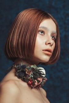 花輪ネックレスを持つ若い赤毛モデルの肖像画を間近します。