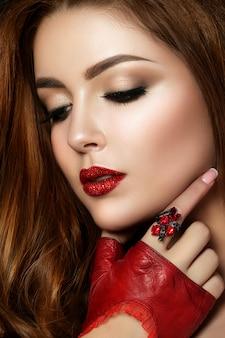 きらめきと茶色のスモーキーな目で赤い唇を身に着けている若い赤毛の女性の肖像画を閉じます。完璧な眉毛。現代のファッションが構成しています。