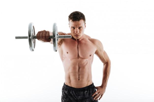 Портрет конца-вверх молодой серьезной разминки мышечного человека с гантелью