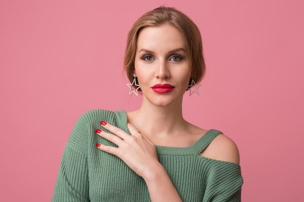 Макро портрет молодой сексуальной привлекательной женщины, стильный макияж, красные губы, зеленый свитер, модель позирует в студии, изолированные, розовый фон, серьги, глядя в камеру