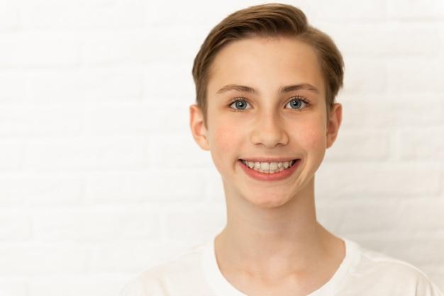 Крупным планом портрет молодой улыбающийся милый подросток на белом фоне