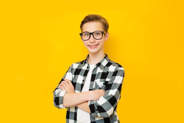 黄色の背景に若い笑顔のかわいいティーンエイジャーの肖像画を閉じる