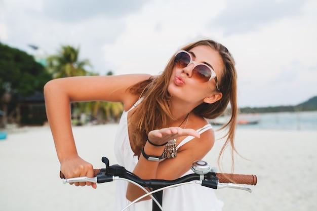 태국에서 여름 휴가를 여행하는 자전거 선글라스에 열대 해변을 타고 흰 드레스에 젊은 웃는 여자의 초상화를 닫습니다
