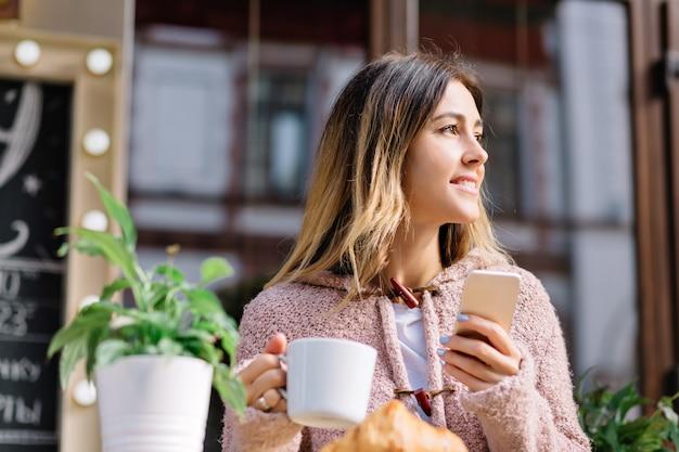 通りのカフェテリアに座っている若いスタイルの女性の肖像画をクローズアップ
