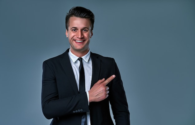 Крупным планом портрет молодого успешного парня-брокера фондового рынка брюнет на чистом сером фоне, он улыбается, носит костюм с галстуком и указывает пальцем на copyspace