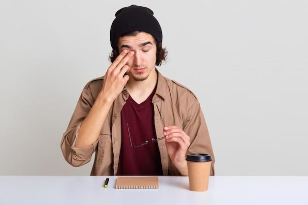 Крупным планом портрет молодой небритый мужчина с волнистыми волосами, сидя за столом, имеет боль в глазах, снимает очки, человек носит небрежно, пьет кофе и записывает что-то в своей записной книжке.