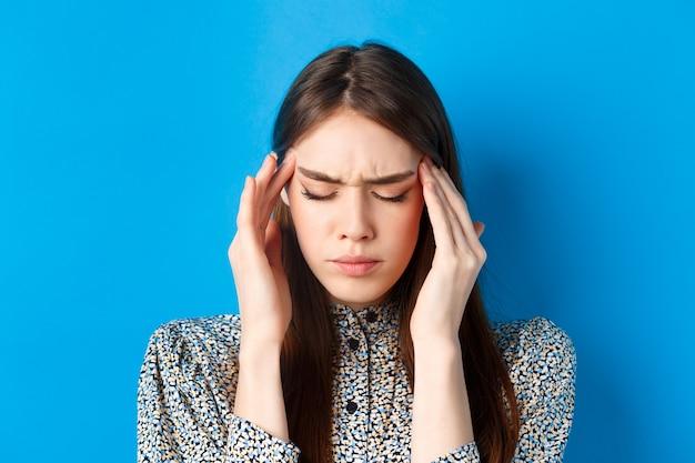 Крупным планом портрет молодой женщины, которая плохо себя чувствует, касается головных висков и хмурится от головной боли, страдает мигренью, стоя на синем.