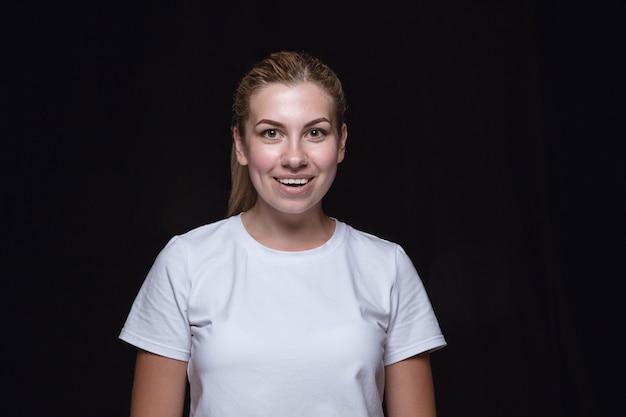 黒に分離された若い女性の肖像画をクローズアップ女性モデルの本当の感情。笑顔、幸せな気持ち。顔の表情、純粋で明確な人間の感情の概念。