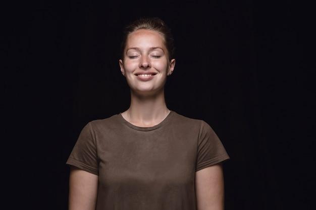黒い空間に孤立した若い女性の肖像画を閉じます。目を閉じた女性モデルの本当の感情の写真撮影。考えて笑う