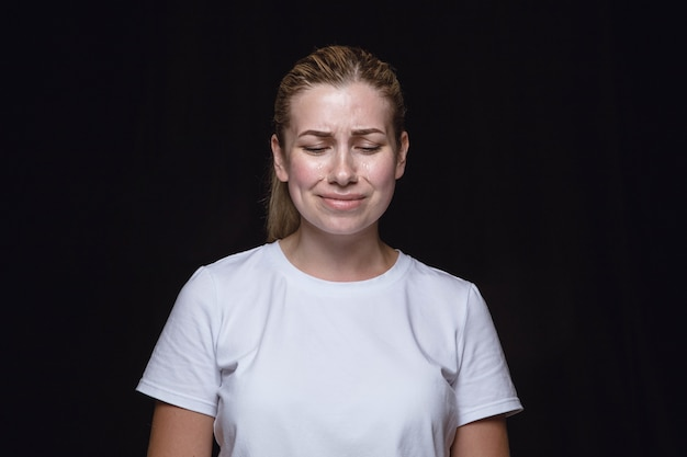 검은 스튜디오 배경에 고립 된 젊은 여자의 초상화를 닫습니다. 여성 모델의 실제 감정이 담긴 포토 샷. 눈을 감고 슬프고 절망적 인 울음. 표정, 인간의 감정 개념.