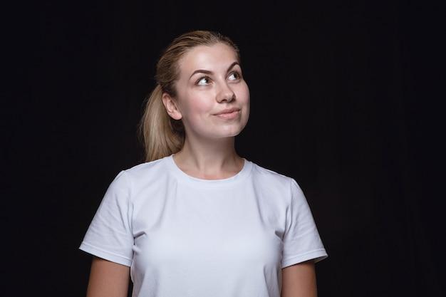 검은 스튜디오 배경에 고립 된 젊은 여자의 초상화를 닫습니다. 여성 모델의 실제 감정이 담긴 포토 샷. 꿈꾸고 웃고, 희망적이고 행복합니다. 표정, 인간의 감정 개념.
