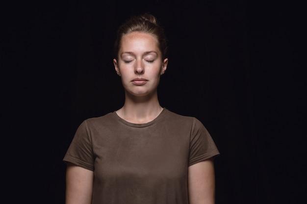 Закройте вверх по портрету молодой женщины изолированной на черной предпосылке студии. фотоснимок реальных эмоций девушки-модели с закрытыми глазами. вдумчивый. выражение лица, концепция человеческой природы и эмоций.