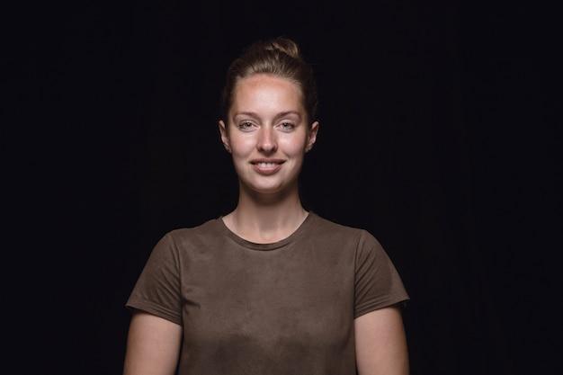 검은 스튜디오 배경에 고립 된 젊은 여자의 초상화를 닫습니다. 웃고, 행복한 기분.