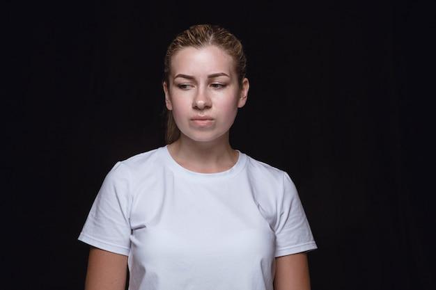 黒のスタジオの壁に分離された若い女性の肖像画を閉じる