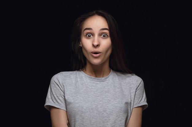 黒い壁に隔離された若い女性の肖像画を閉じます。女性モデルの本当の感情。不思議で、刺激的で、驚いた。顔の表情、人間の感情の概念。