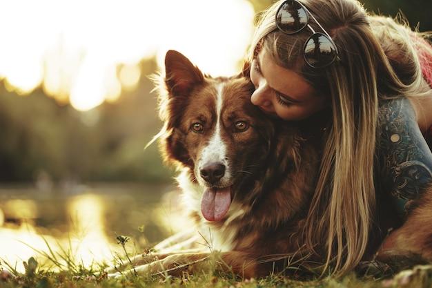 Крупным планом портрет молодой женщины, целующей ее собаку в парке