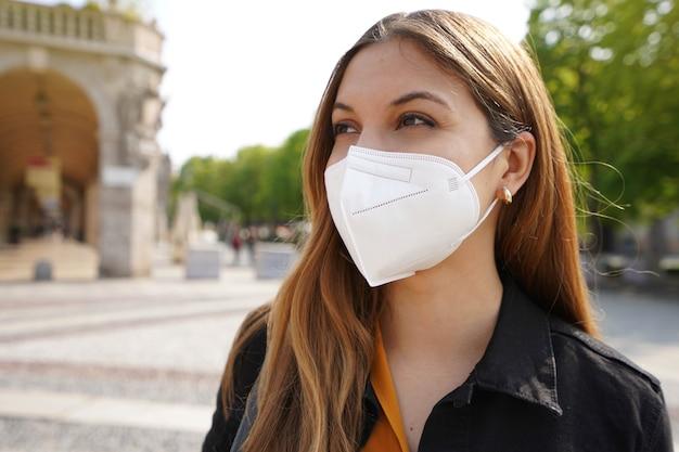 屋外で保護マスクkn95ffp2を着用しながら横を向いている若い女性の肖像画を閉じる
