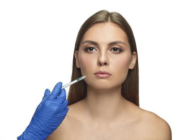 ホワイト スタジオの背景に若い女性のクローズ アップの肖像画。充填手術手順。唇増強。女性の健康と美容、美容、セルフケア、ボディケア、スキンケアのコンセプト。老化防止。 無料写真