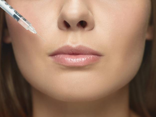 ホワイト スタジオの背景に若い女性のクローズ アップの肖像画。充填手術手順。唇増強。女性の健康と美容、美容、セルフケア、ボディケア、スキンケアのコンセプト。老化防止。