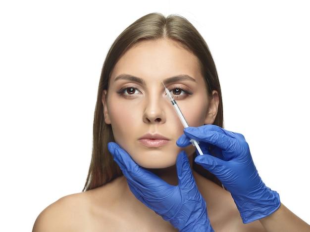 白い壁に若い女性のクローズアップの肖像画。充填手術手順。顔の輪郭。女性の健康と美容、美容、セルフケア、ボディケア、スキンケアのコンセプト。老化防止。