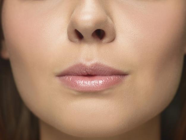 若い女性の顔のクローズアップの肖像画。手入れの行き届いた肌と大きな唇を持つ女性モデル。女性の健康と美容、美容、化粧品、セルフケア、ボディケア、スキンケアのコンセプト。老化防止。