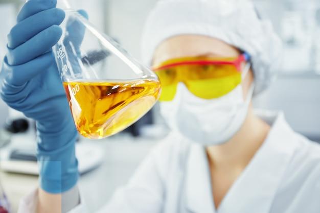 노란색 액체와 함께 테스트 튜브를 들고 젊은 여자의 손의 초상화를 닫습니다