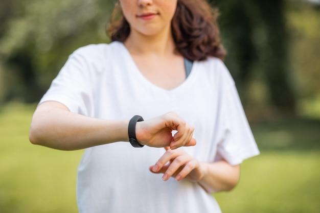 Закройте вверх по портрету касания молодой женщины и проверяет ее умные часы. концепция современного устройства и велнеса