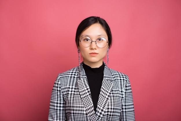 Крупным планом портрет молодой женщины в костюме и круглых очках, стоя над розовой стеной